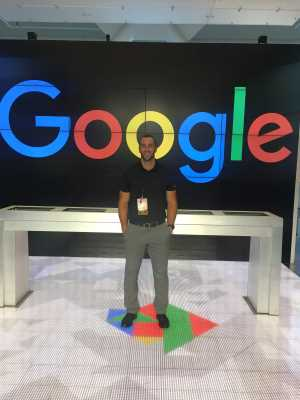 Standing in front of the Google logo at the Google Headquarters